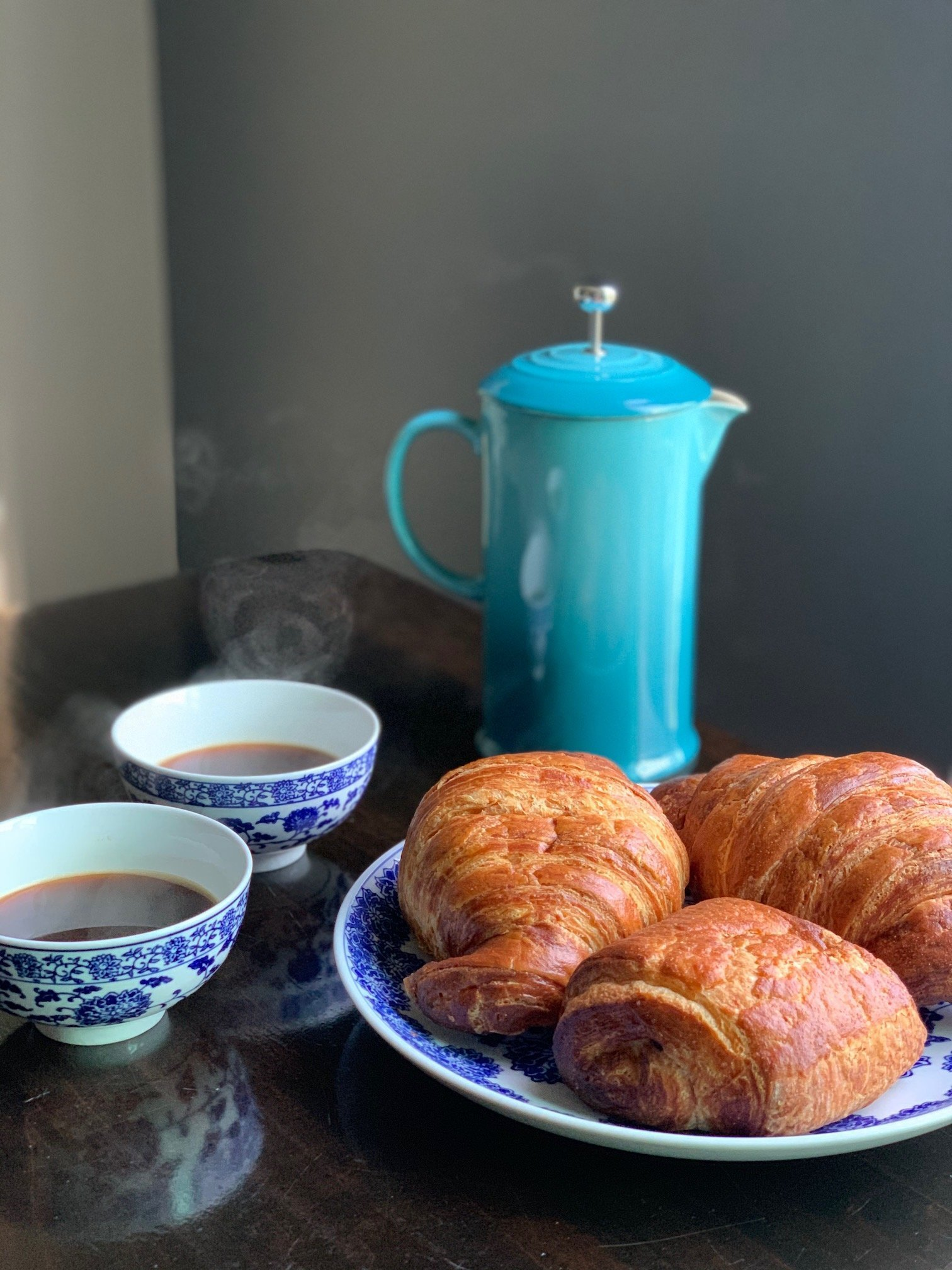 steaming hot coffee with a blue french press and croissants